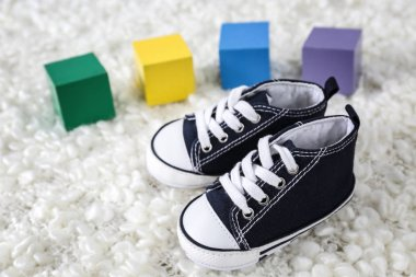 Cute baby shoes and colorful cubes