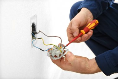 Electrician disassembling wall socket