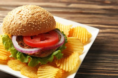 Tasty burger with potato chips