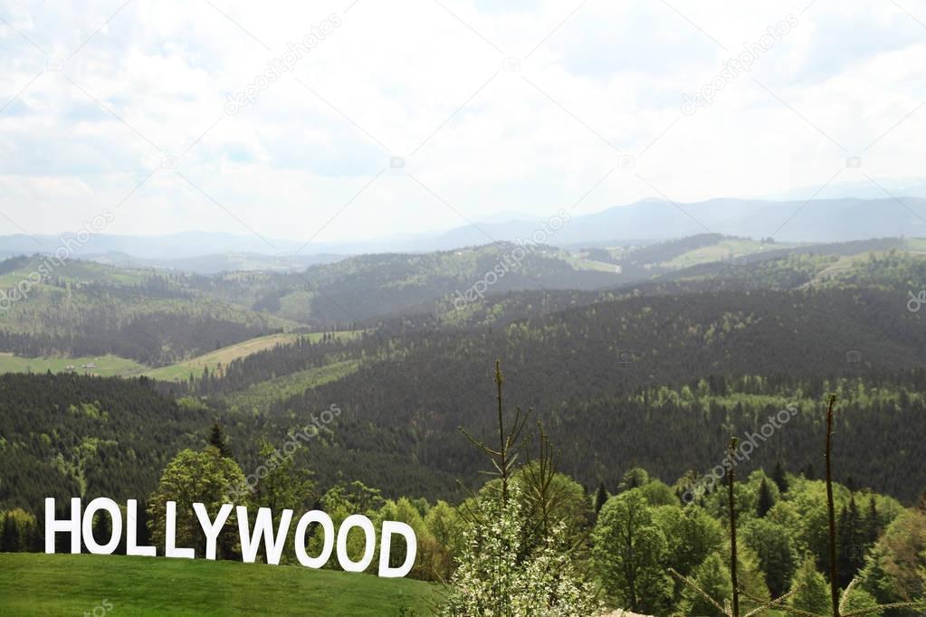 Word HOLLYWOOD over landscape