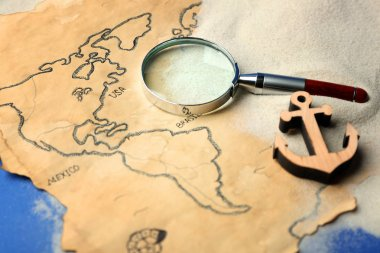 Magnifier and wooden anchor on old map