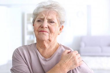 Elderly woman suffering from pain in shoulder