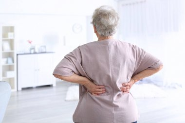 Elderly woman suffering from backache at home