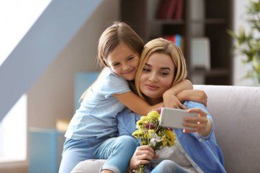 Beautiful young woman and her daughter taking selfie while sitting on sofa at home. Mother's day concept