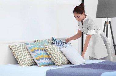 Female chambermaid making bed