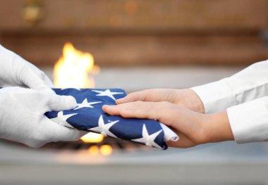 Hands holding folded American flag