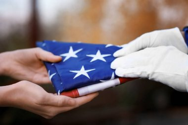 Hands holding folded American flag