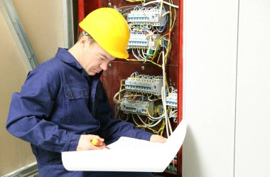Electrician checking connections in distribution board according to wiring diagram