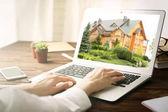 Online nakupování koncept. Žena hledá dům na stránkách trhu nemovitostí