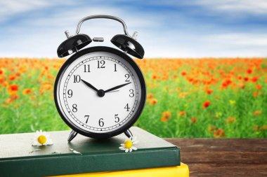 Alarm clock against nature landscape
