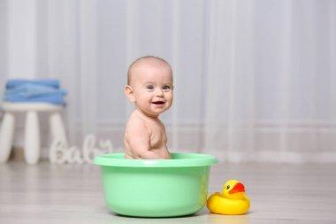 Cute baby in plastic basin