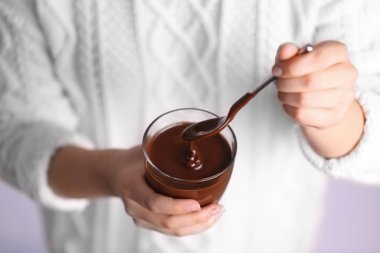 Woman holding cup with chocolate mousse