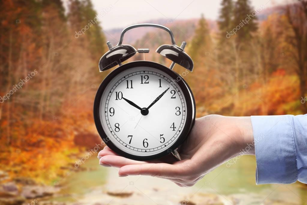 Alarm clock against nature landscape