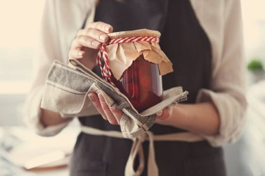 Woman in apron holding strawberry jam