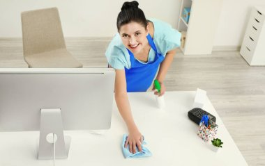 woman cleaning computer table
