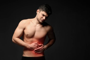 Young man suffering from abdominal pain on black background. Health care concept