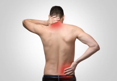 Young man suffering from back pain on light background. Health care concept