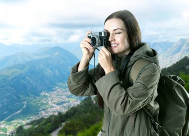 Young woman taking photo of beautiful landscape