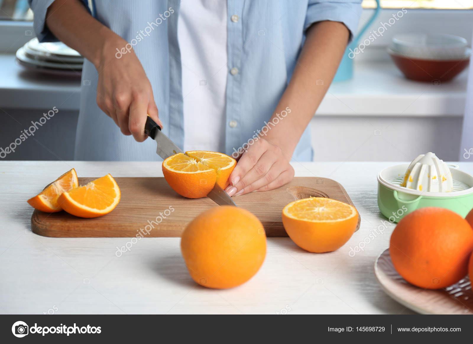 Weibliche Hände schneiden orange — Stockfoto © belchonock #145698729