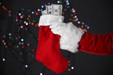 Santa Claus hand holding Christmas stocking