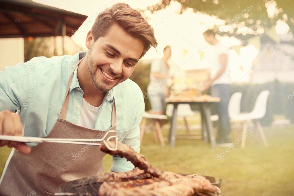 young man preparing barbecue steaks