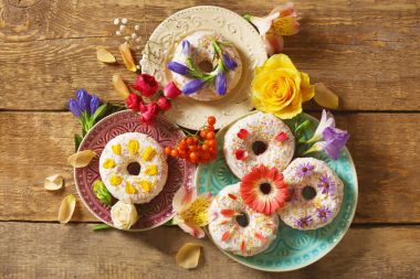 plates with delicious donuts and colourful flowers
