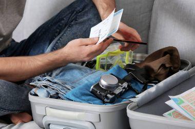 Man packing grey suitcase