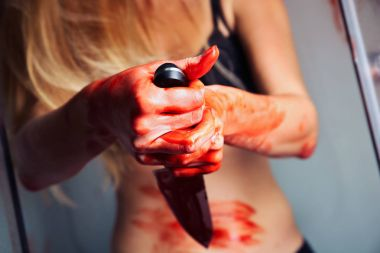 Bloody hands with knife