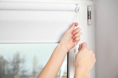 hands installing window blinds