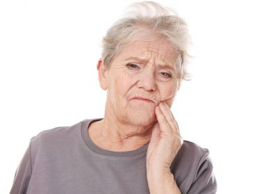 Elderly woman suffering from toothache
