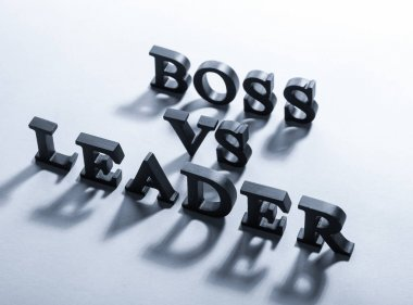Black letters forming text BOSS VS LEADER on grey background