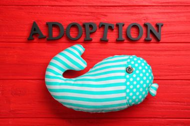 Word ADOPTION and whale toy