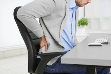 Man with back pain in armchair at office, closeup