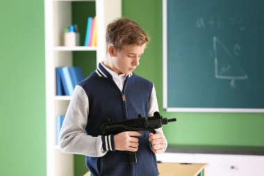 Teenage boy with gun in classroom