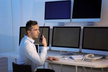 Handsome security guard in surveillance room