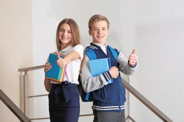 Teenagers with books standing on stairs