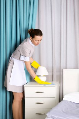 Chambermaid cleaning bedside table