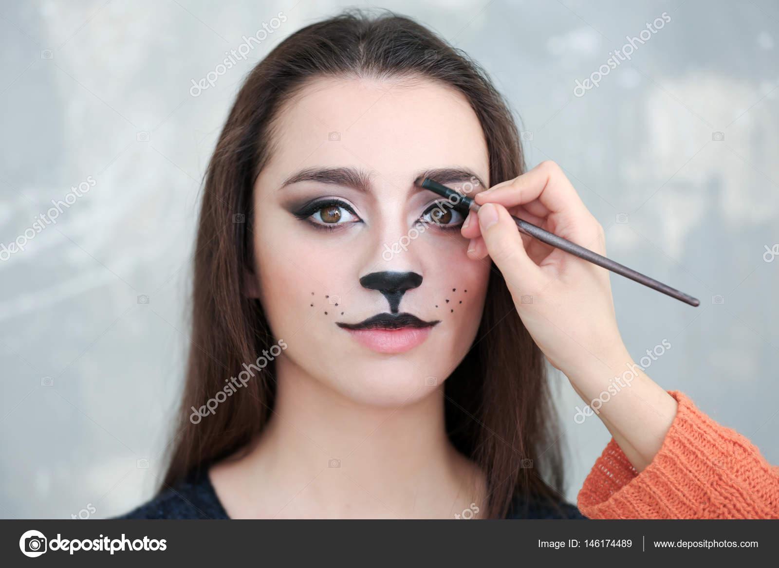 eff6ffe7c Visagiste aplicar el maquillaje de gato en la cara de hermosa mujer joven  en el salón