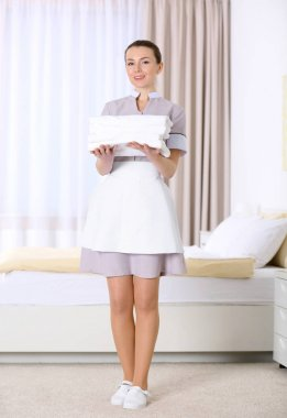 chambermaid holding pile of towels