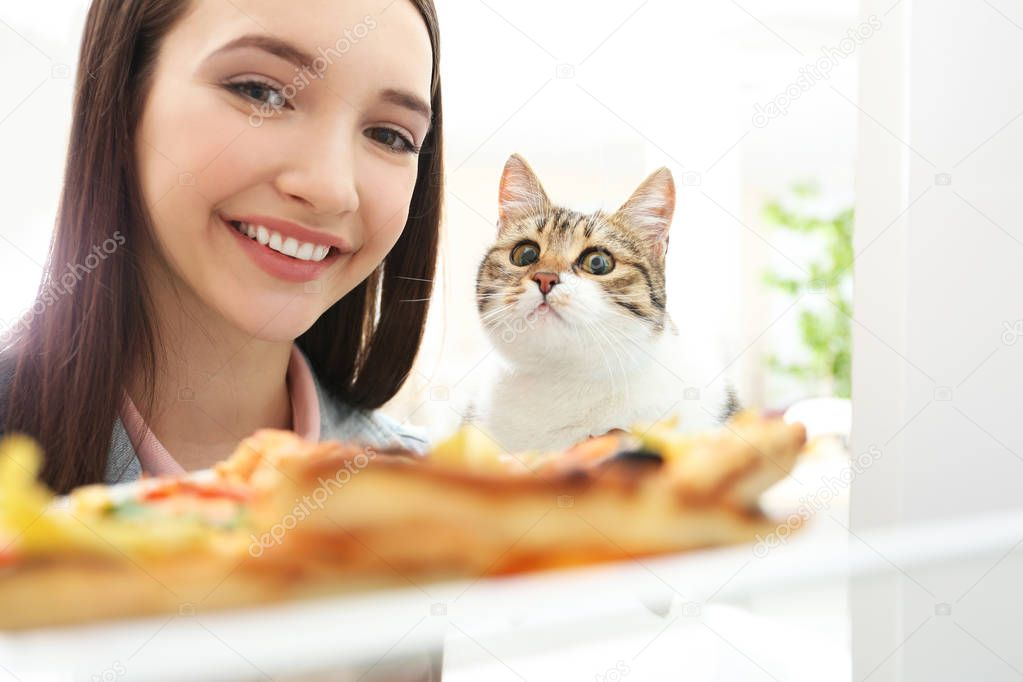Young woman and cute cat going to eat tasty pizza from refrigerator