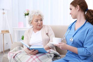 Nurse giving cup of tea to elderly women in light room