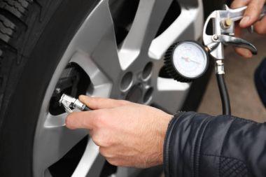 Auto mechanic checking tire pressure