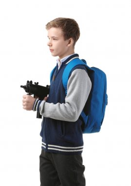 Teenage boy with backpack holding gun on white background