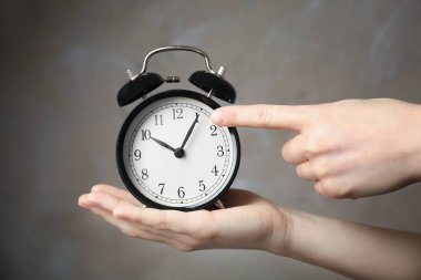 hands holding alarm clock