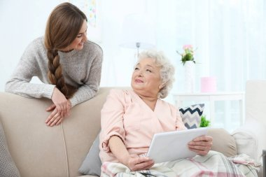 Beautiful girl with grandmother using tablet at home