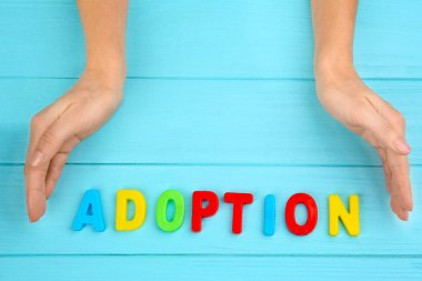 Female hands and word ADOPTION