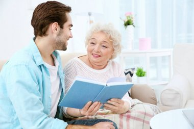 Young man with grandmother reading book on couch at home