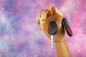 Wooden hand holding car keys