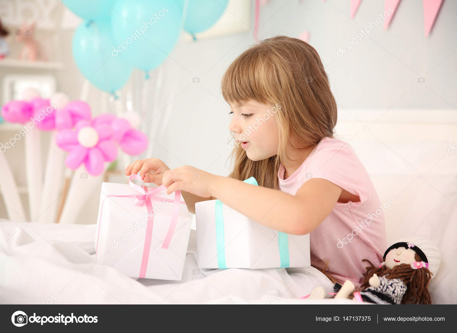 Cute Birthday Girl Opening Boxes With Presents While Sitting On Bed