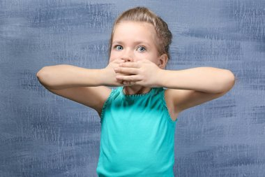 little girl covering mouth with hands